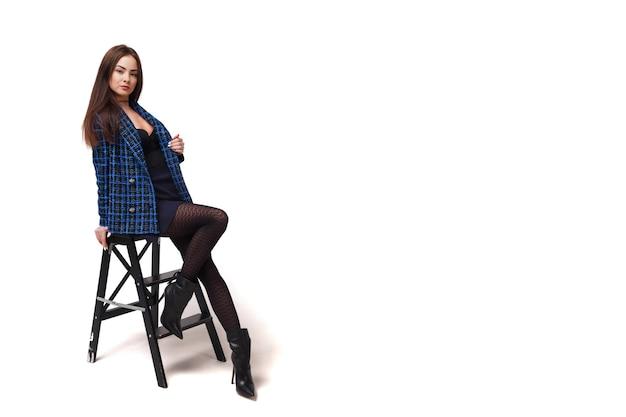 Портрет стильной молодой коммерсантки в синем пальто и юбке на белом изолированном фоне. милая сексуальная дама позирует и показывает эмоции. понятие стиля, моды в бизнесе. копировать пространство