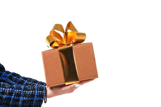 Портрет стильной молодой деловой женщины в синем пальто представляет подарочную коробку на белом изолированном фоне. милая сексуальная дама позирует и показывает эмоции. понятие стиля, моды в день святого валентина