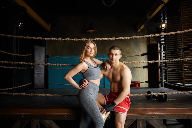 ジムでポーズをとる、ボクシングリングの外に座って、抱きしめて、健康的なアクティブなライフスタイルを選択するスリムな筋肉の体を持つスタイリッシュな若い男性と女性の肖像画。武道、スポーツ、フィットネスの概念