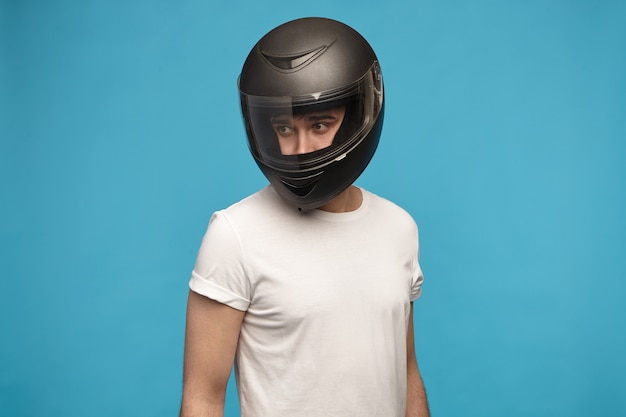 Портрет стильного молодого человека в белой футболке и мотоциклетном шлеме позирует