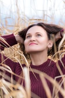 フィールドで乾いた草でポーズをとって茶色のプルオーバーに身を包んだスタイリッシュな若い女性の肖像画。長い巻き毛のブルネットの髪と赤い唇を持つ幸せな女性。