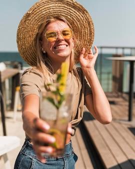 夏のカクテルを楽しむスタイリッシュな若い女性の肖像画