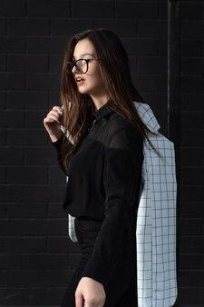 Портрет стильной молодой женщины в очках и черной одежде на черном фоне. вертикальная рама.
