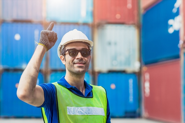 成功した職長の輸送ラテン語のスタッフの肖像は、サングラスをかけた笑顔で輸出入商品のために貨物港で働いています。