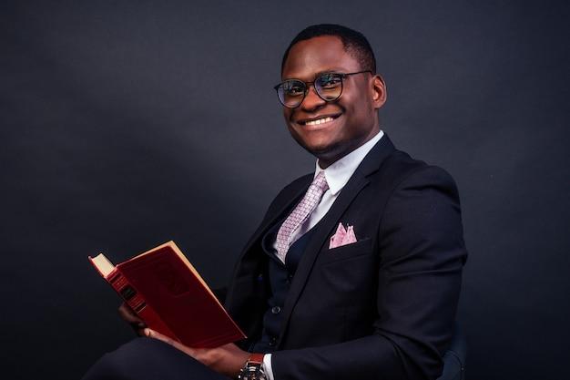 Портрет успешного лидера компании афро-американского бизнесмена в очках, читая книгу на черном фоне. студия выстрел