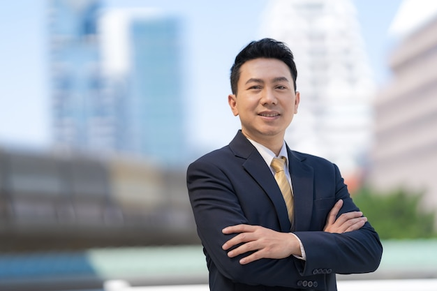 Портрет успешного азиатского бизнесмена, стоящего со скрещенными руками перед современными офисными зданиями