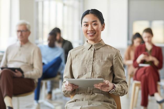 Портрет успешной азиатской бизнес-леди, улыбающейся в камеру, позируя в офисе с людьми в фоновом режиме, копией пространства