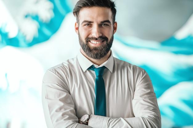 Портрет успешного бородатого кавказского бизнесмена с рубашкой и галстуком, стоя с оружием, пересекли в офисе. наручные наручные часы. морить себя голодом, подпитывать внимание.