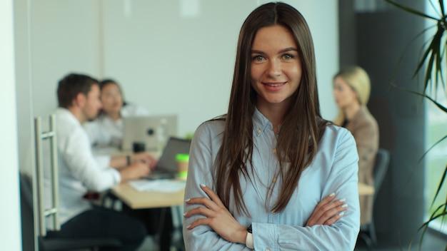 현대적인 회의실에 서 있는 현대적인 사무실 직장에서 카메라를 보고 웃는 팔짱을 끼고 있는 성공적인 아름다운 중역 여성 사업가의 초상화