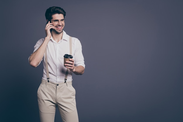 파트너와 전화 말하기 뜨거운 테이크 아웃 커피를 마시는 성공적인 비즈니스 남자의 초상화는 formalwear 셔츠 멜빵 바지 사양을 입고.
