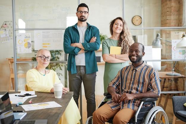 会議の後にオフィスに立っている間カメラに微笑んで成功したビジネスチームの肖像画