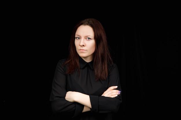 Портрет успешной деловой женщины в черной рубашке со скрещенными руками на черном фоне.