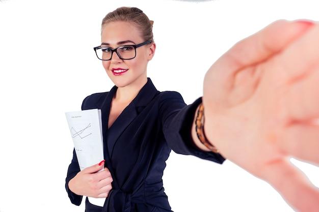 안경 금발 헤어스타일을 한 성공적인 비즈니스 여성의 초상화, 세련된 검은색 정장을 입고 카메라 스튜디오 흰색 격리에서 셀카를 촬영하는 서류 그래프를 들고