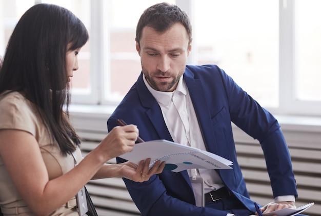 Портрет успешного бизнесмена, разговаривающего с молодой женщиной, сидя в аудитории на бизнес-конференции, копией пространства