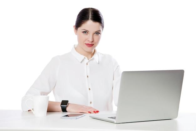 ノートパソコンと一緒に座って笑顔でカメラを見ている白いシャツの化粧で成功した穏やかな魅力的なブルネットの実業家の肖像画。白い背景で隔離の屋内スタジオショット。