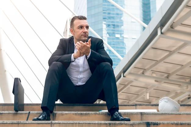 Портрет успешного кавказского бизнесмена хлопать и сидя на лестнице.