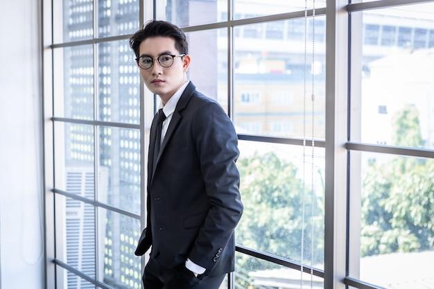 성공적인 느낌의 우승자 초상화 안경을 쓴 잘생긴 젊은 아시아 사업가의 초상화는 사무실 방 배경에서 창을 바라보는 파란색 재킷과 파란색 셔츠를 입은 남자의 비즈니스 정장을 입고 있습니다.