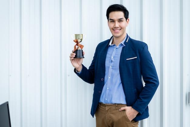 사무실 방 배경에서 챔피언 컵을 들고 있는 잘생긴 젊은 아시아 사업가가 비명을 지르는 성공적인 느낌의 승자의 초상화.