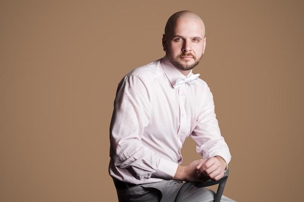 Портрет успешного красивого бородатого лысого мужчины в светло-розовой рубашке и белом банте, сидящего на стуле и уверенно смотрящего в камеру. крытая студия выстрел, изолированные на коричневом фоне.