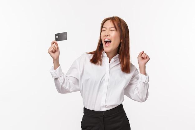 成功した幸せで安心したアジアの女性の肖像画は嬉しそうに叫び、手を挙げて、クレジットカードを持っているように応援し、チャンピオンのように目を閉じて、