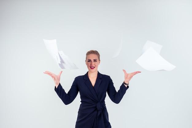 成功した幸せなビジネス女性の肖像画メガネブロンドの髪型完璧なメイクアップ赤い唇スタイリッシュな黒いスーツで紙を投げる、スタジオの白い背景で分離。締め切りの自由