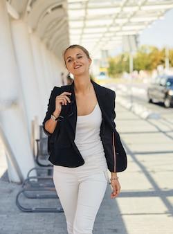 通りで働く彼女の方法で成功した幸せなビジネスウーマンの肖像画