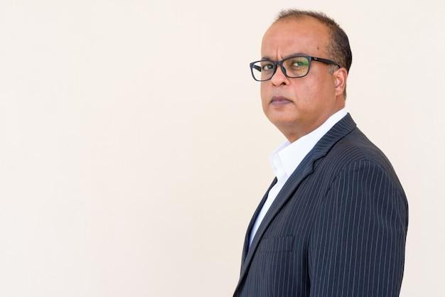 Портрет успешного индийского бизнесмена против простой стены на открытом воздухе
