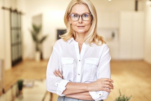 ポーズをとっている間カメラを見ているアイウェアで成功した成熟した金髪の実業家の肖像画