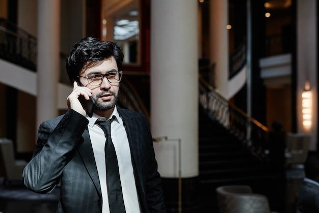 햇빛이 비치는 호텔 로비에서 스마트폰으로 말하는 성공적인 중동 사업가의 초상화, 복사 공간