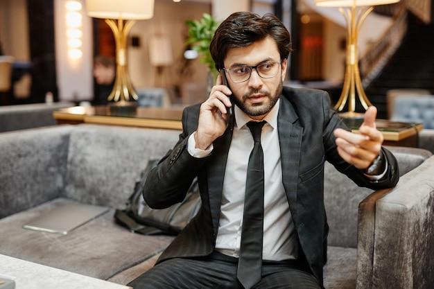 호텔 로비의 안락의자에 앉아 스마트폰으로 말하는 성공적인 중동 사업가의 초상화