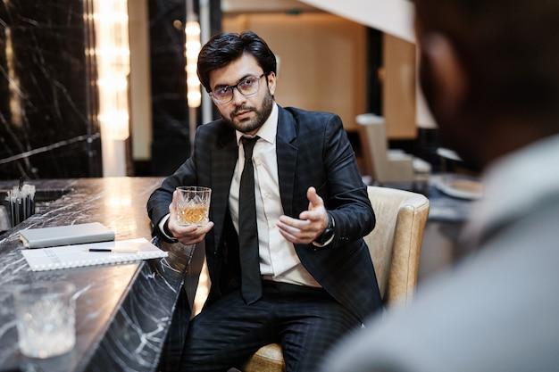 비즈니스 여행 중 호텔 바에서 파트너와 이야기하는 성공적인 중동 사업가의 초상화, 공간 복사