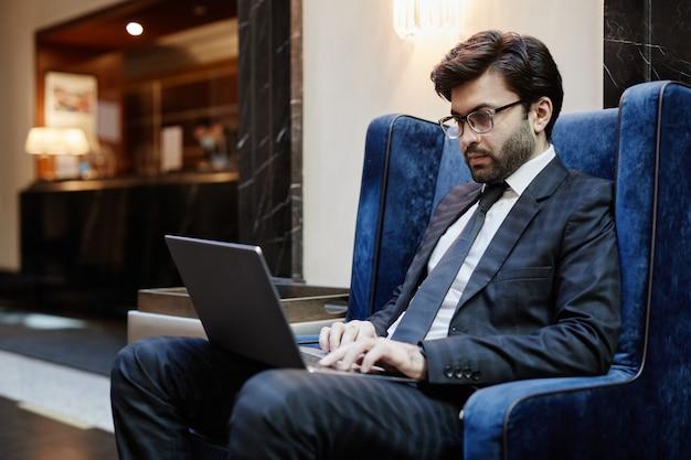비즈니스 여행을 위해 호텔 로비에서 일하는 동안 노트북을 사용하는 성공적인 중동 사업가의 초상화, 복사 공간