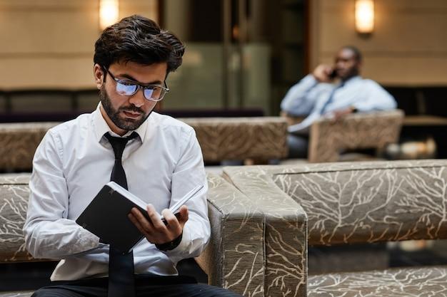 호텔 라운지에서 일하는 동안 노트북에 글을 쓰는 성공적인 중동 사업가의 초상화, 복사 공간