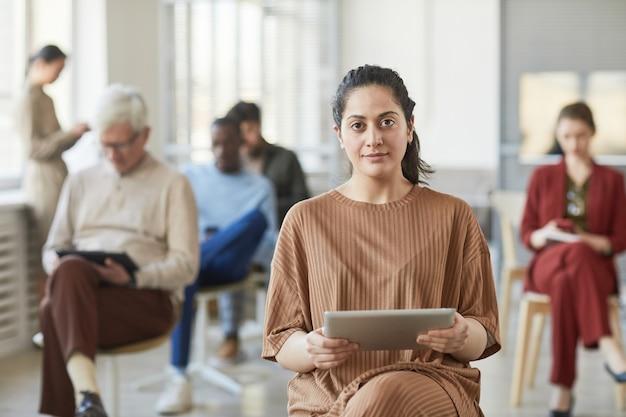 Портрет успешной ближневосточной бизнес-леди, смотрящей в камеру, позируя в офисе с людьми в фоновом режиме, копией пространства