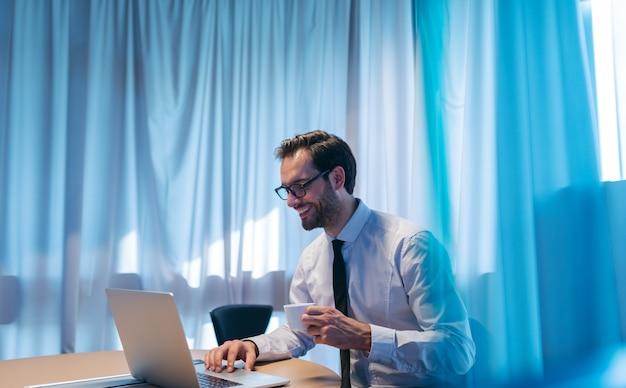 Портрет успешного улыбающегося бизнесмена, использующего ноутбук и пьющего эспрессо, сидя в своем офисе.