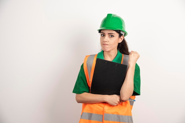 헬멧 및 안전 오렌지 조끼를 입고 성공적인 여자 생성자의 초상화. 고품질 사진