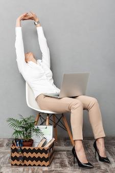 孤立した、オフィス用品と椅子に座ってラップトップを使用して成功した女性の肖像画