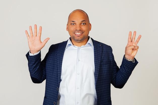 成功した若いアフリカ系アメリカ人のビジネスマンの男の肖像画、8番に指で示して、笑顔、自信を持って幸せです。男は8本の指を見せています。番号8。