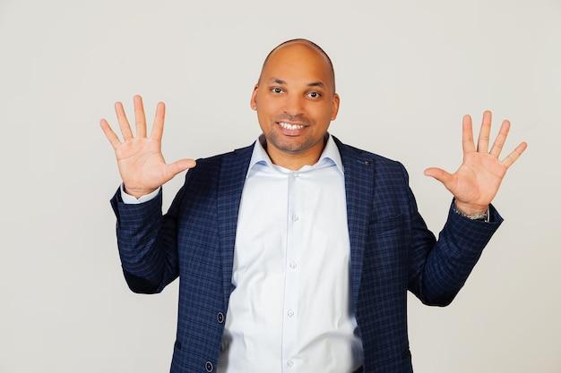成功した若いアフリカ系アメリカ人のビジネスマンの男の肖像画、10番に指で示して、笑顔、自信を持って幸せです。男は10本の指を見せます。番号10。灰色の壁に立っています。
