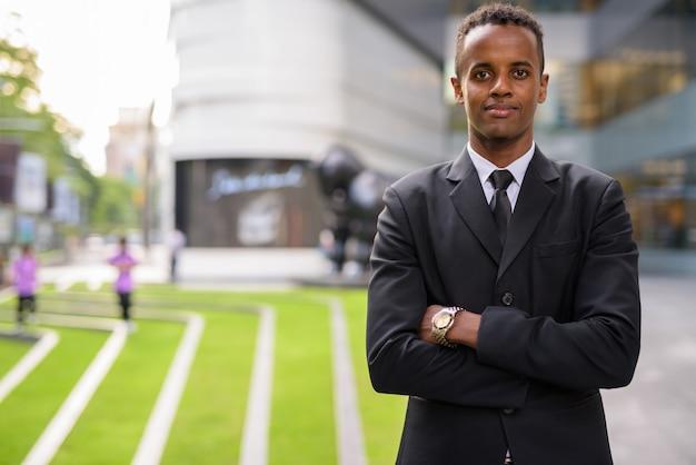 腕を組んで屋外で成功した若いアフリカの実業家の肖像画
