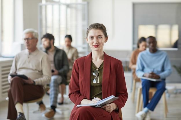 Портрет успешной молодой бизнес-леди, улыбаясь в камеру, позирует в офисе с людьми в фоновом режиме, копией пространства