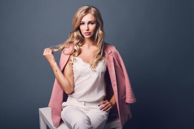 Портрет успешной молодой соблазнительной блондинки в розовой пастельной куртке, сидящей на столе