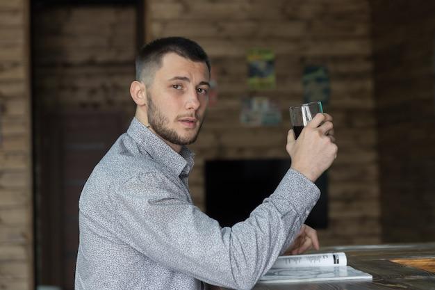 バーカウンターの近くに立って、理髪店で飲み物を飲む成功した若いスタイリッシュな男の肖像画