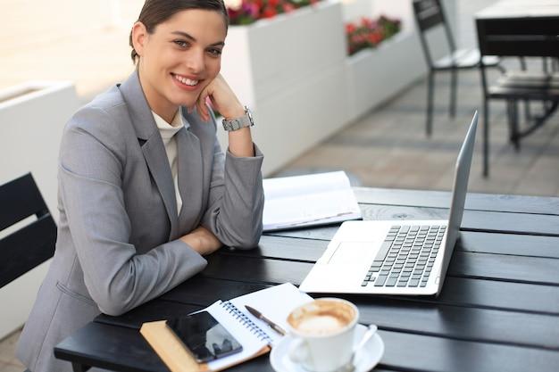 Портрет успешной молодой женщины с ноутбуком в уличном кафе.