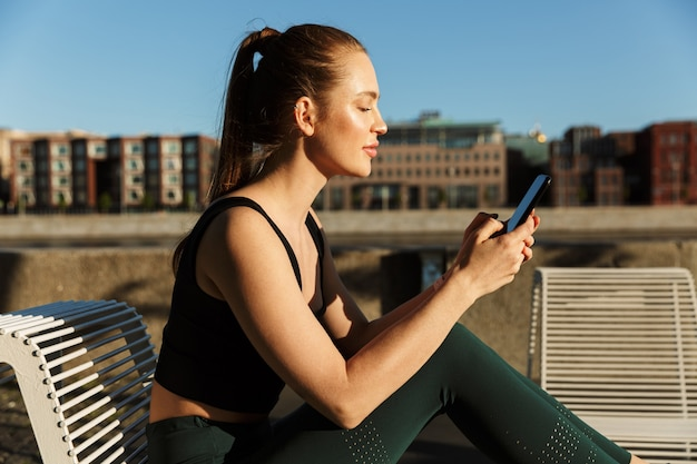 Портрет залитой солнцем спортивной женщины в спортивном костюме, держащей смартфон и сидящей на стуле во время тренировки на городской улице