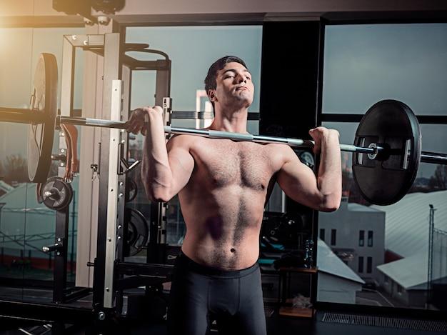 灰色のバーベルとジムでワークアウトスーパーフィットの筋肉の若い男の肖像画