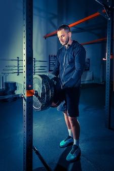 バーベルとジムで運動しているスーパーフィットの筋肉の若い男の肖像画