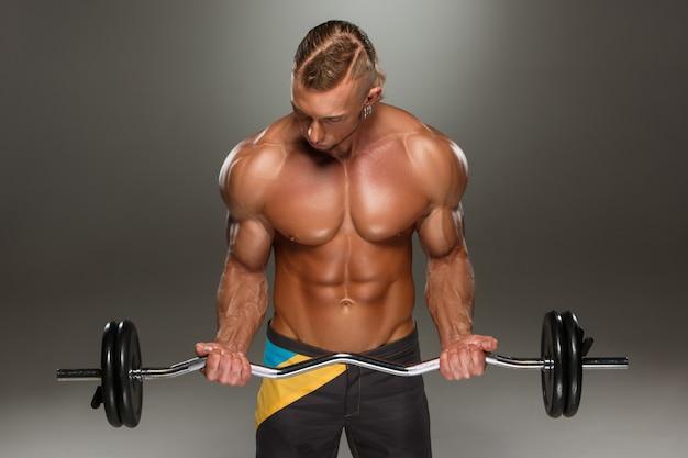スーパーの肖像画は、ジムでワークアウト筋肉の若い男に合います。