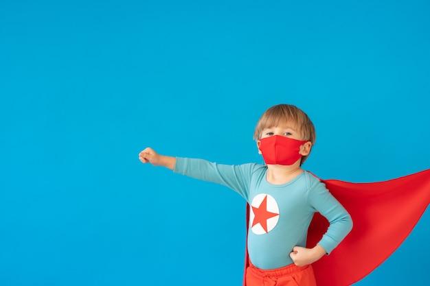 Портрет малыша супергероя против стены голубой бумаги.