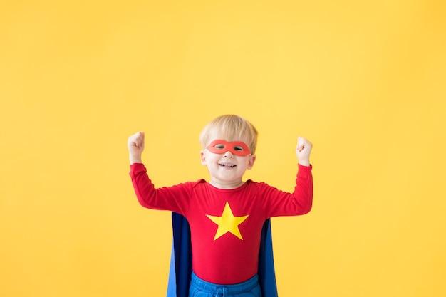 노란색 배경에 슈퍼 히어로 슈퍼 히어로의 초상화 마스크와 망토를 입고 행복한 아이